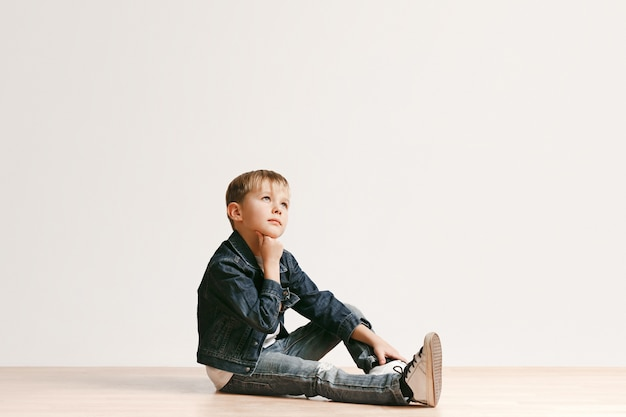 Retrato de menino bonitinho com roupas jeans elegantes, olhando para a câmera contra a parede branca do estúdio. conceito de moda infantil