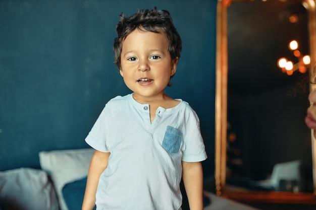 Retrato de menino bonito alegre de pele escura brincando em casa sozinho, olhando para frente com um sorriso alegre.