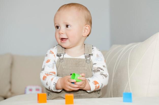 Retrato de menino bonito caucasiano jogando blocos coloridos em formas diferentes. aprendendo jogando o conceito de escola em casa de educação de treinamento do cérebro.