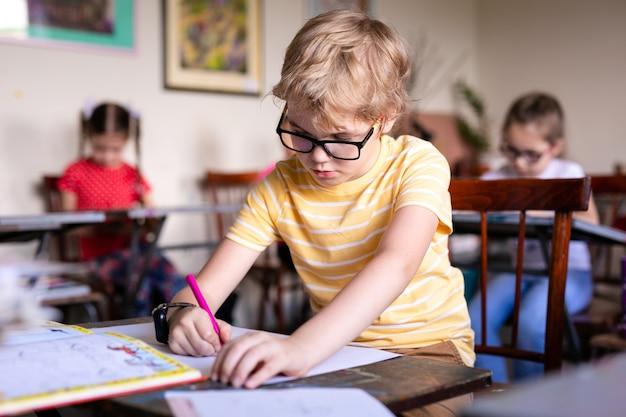 Retrato de menino bonito com caneta de desenho e papel na mesa na sala de aula.