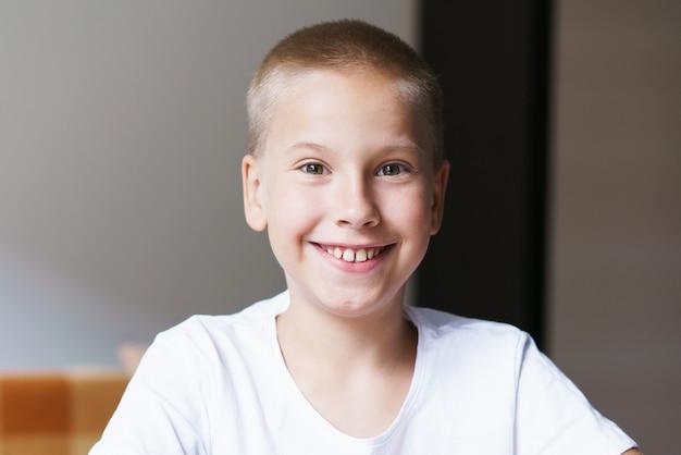 Retrato de menino bonito com sorriso branco como a neve em closeup de camiseta branca olha para a câmera enquanto está sentado no ...