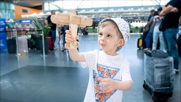 Retrato de menino bonito da criança brincando com o avião de brinquedo no terminal do aeroporto.