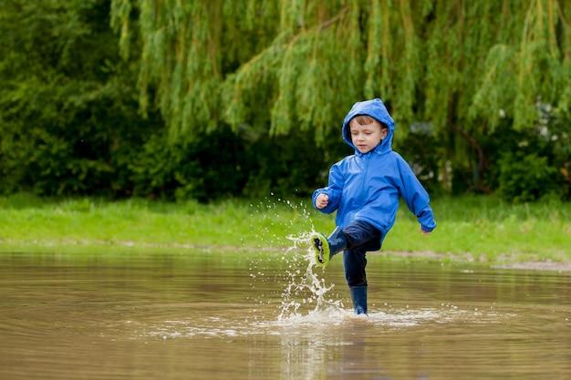 Retrato de menino bonito garoto brincando com navio feito à mão.