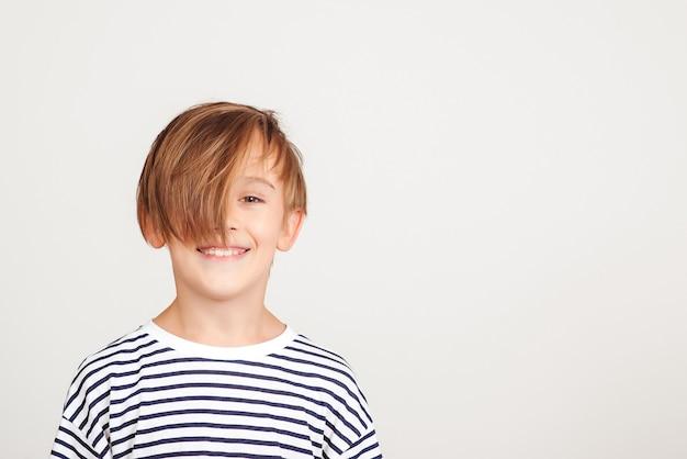 Retrato de menino bonito. menino sorridente, posando no estúdio. estilo e moda infantil. menino feliz com um penteado elegante. infância feliz e emoções positivas.