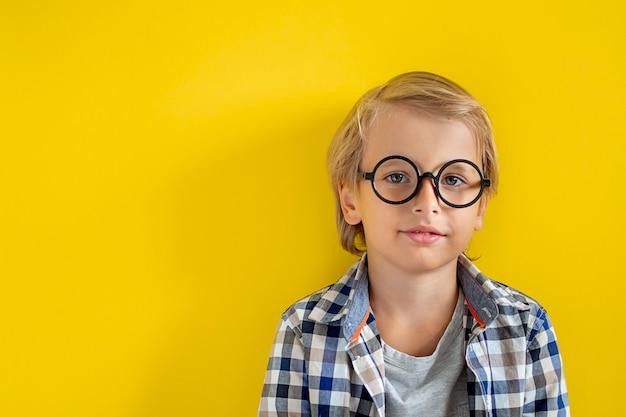 Retrato de menino branco loiro bonito e inteligente com uma camisa xadrez em fundo amarelo. 1º dia de setembro. educação e volta ao conceito de escola. aluno criança pronto para aprender e estudar.