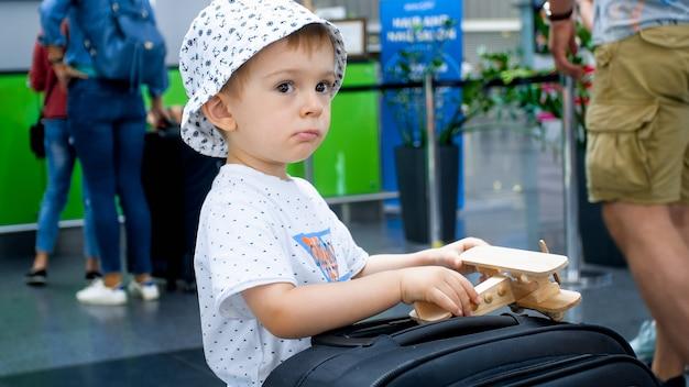 Retrato de menino brincando com o avião de brinquedo e a mala no terminal do aeroporto.