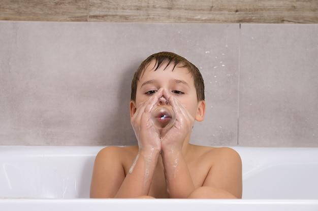 Retrato de menino brincando com sabão, shampoo ou gel no banheiro, criança tomando banho e infla bolhas de sabão