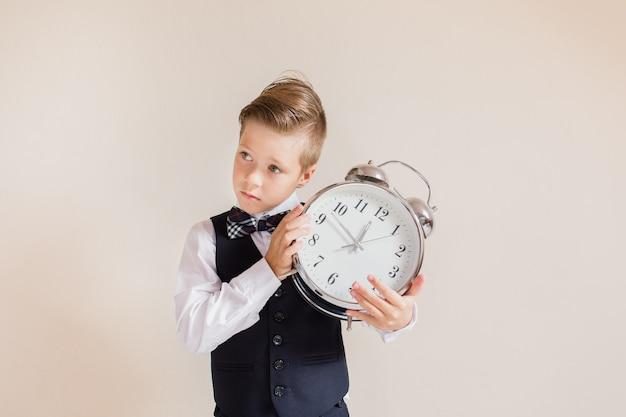 Retrato de menino caucasiano de terno cinza com relógio grande. menino bonito, segurando e ouvindo o relógio. criança de volta à escola. conceito de educação e tempo.