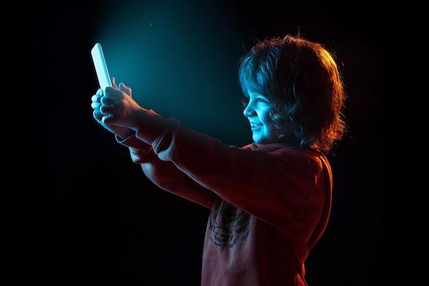 Retrato de menino caucasiano isolado no escuro do estúdio sob luz de néon