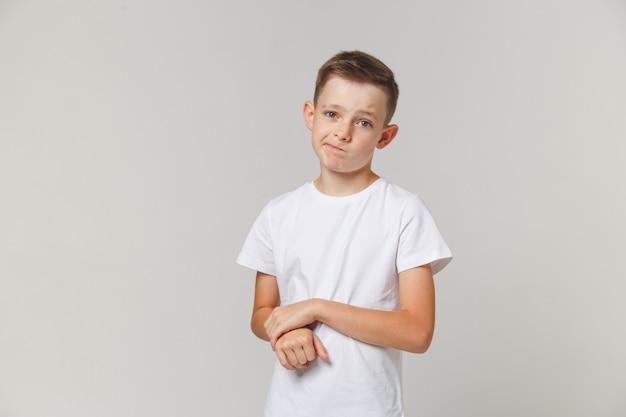 Retrato de menino chateado em pé com os braços cruzados isolado sobre fundo branco