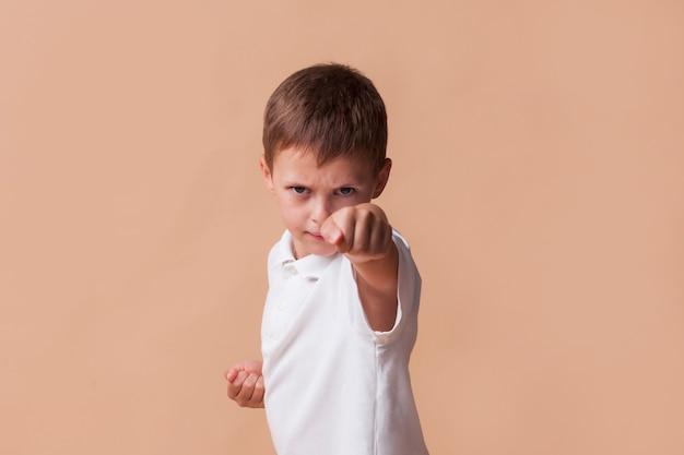 Retrato, de, menino, clinging, seu, punho, para, luta, ligado, bege, fundo