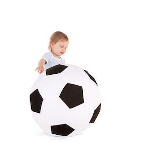 Retrato de menino com bola de futebol na parede branca