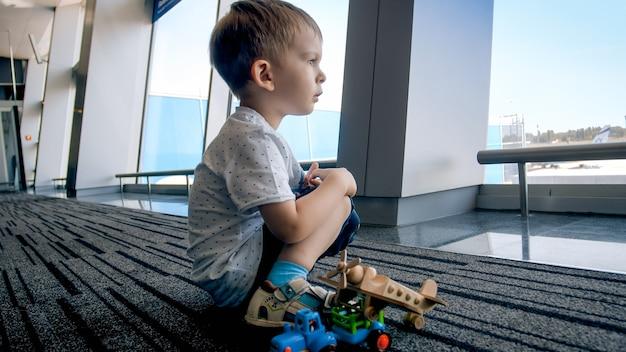Retrato de menino com brinquedos sentado no terminal do aeroporto e olhando pela janela.
