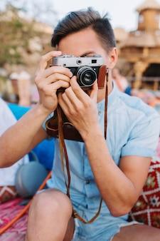 Retrato de menino com cabelo preto curto, segurando uma câmera retro e tirando fotos, enquanto está sentado em um café ao ar livre