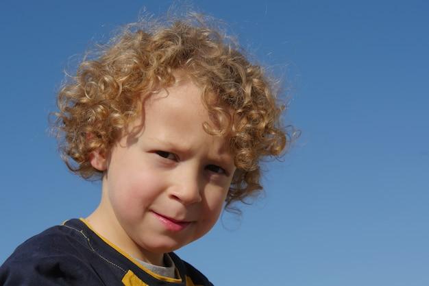 Retrato de menino com cabelos loiros e encaracolados