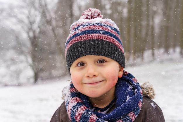 Retrato de menino com chapéu quente e cachecol snood no parque no inverno. criança feliz curtindo a neve e o clima gelado.