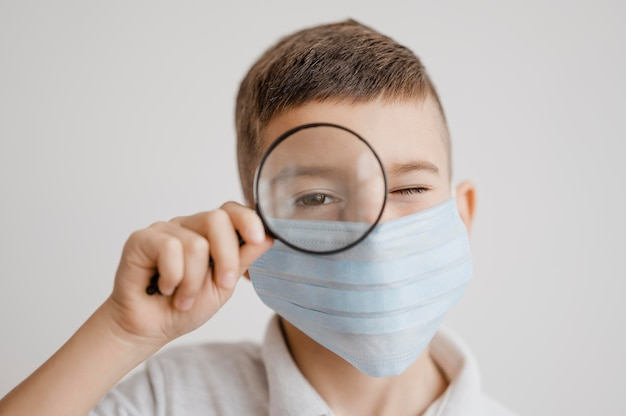 Retrato de menino com máscara médica usando uma lupa na aula