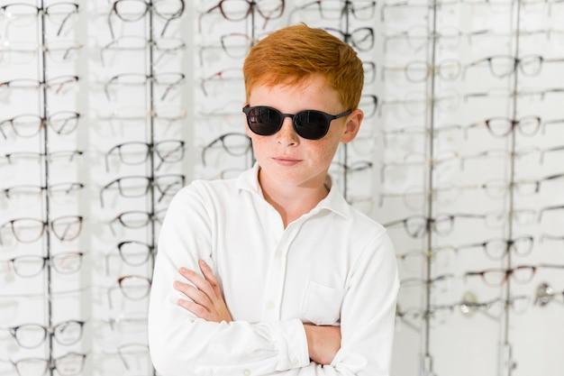Retrato de menino com óculos pretos de pé contra o fundo de óculos