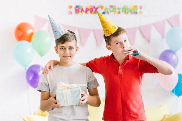 Retrato, de, menino, com, seu, amigo, segurando, presente aniversário