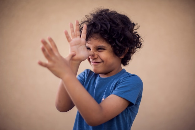 Retrato de menino criança feliz com cabelos cacheados, mostrando o gesto de provocação. conceito de crianças e emoções