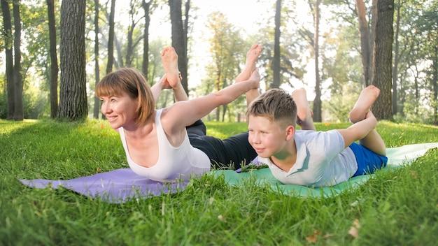 Retrato de menino de 12 anos fazendo exercícios de ioga com sua mãe no parque. família meditando e se alongando na floresta