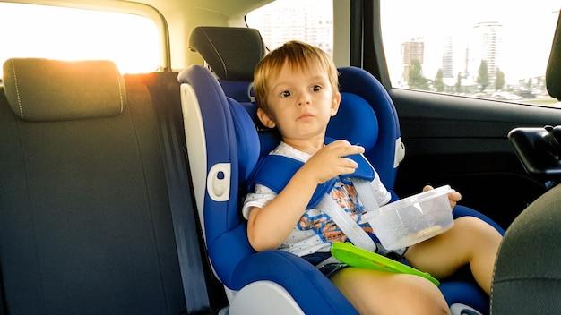 Retrato de menino de 3 anos de idade, sentado na cadeira de segurança infantil no carro e comendo biscoitos. crianças viajando de automóvel