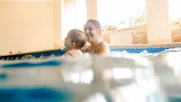 Retrato de menino de criança de 3 anos de idade com a jovem mãe nadando na piscina coberta. criança aprendendo a nadar e praticar esportes. família curtindo e se divertindo na água