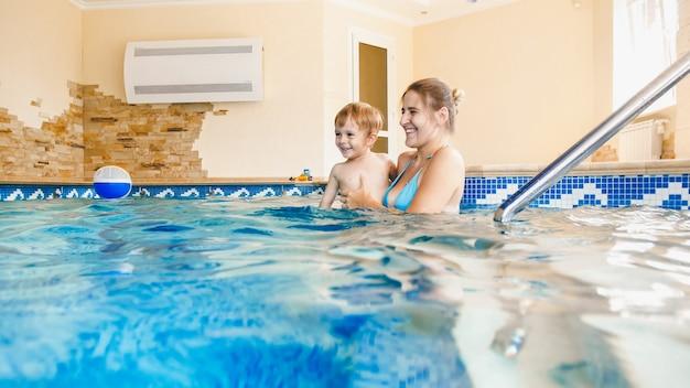 Retrato de menino de criança de 3 anos de idade com a jovem mãe nadando na piscina coberta. criança aprendendo natação e esportes