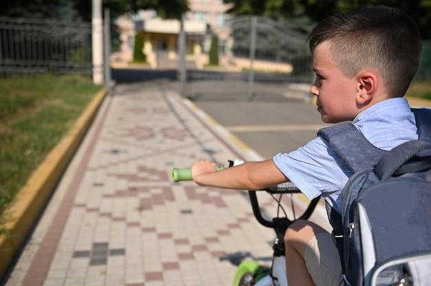Retrato de menino de escola bonito com bolsa escola, andar de bicicleta para o estabelecimento de escola. criança voltando para a escola. vista de trás
