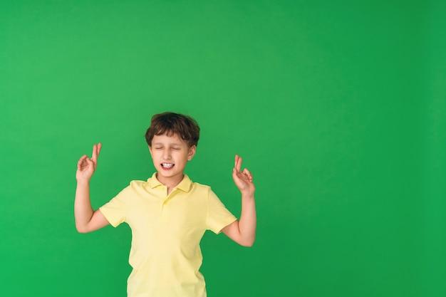Retrato de menino de sete anos de idade, dedos cruzados e desejando boa sorte