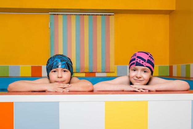 Retrato de menino e menina caucasianos em uma piscina