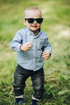 Retrato de menino elegante posando no parque no verão