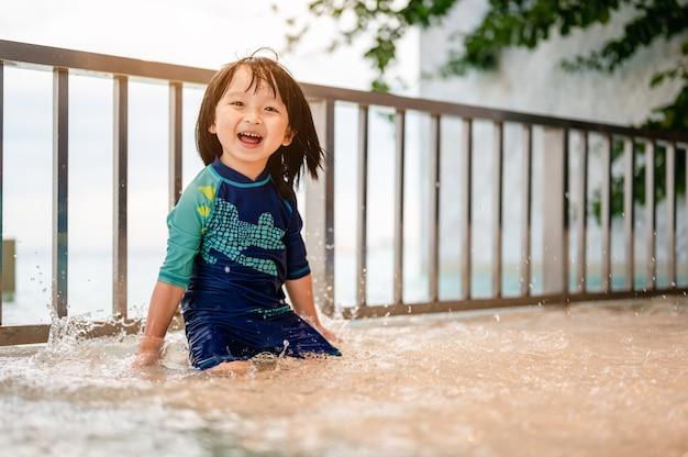 Retrato de menino em fato de banho a espirrar as mãos na piscina. hawin