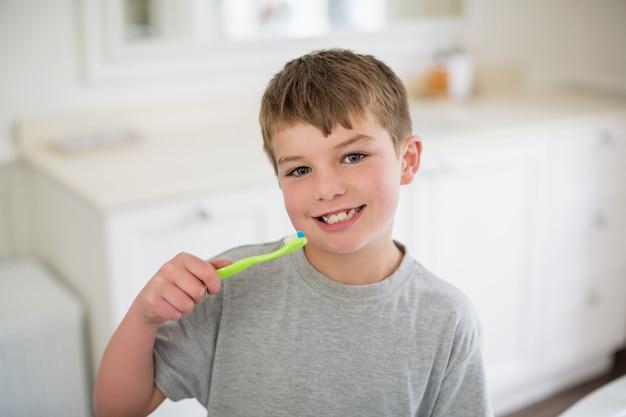 Retrato de menino, escovar os dentes no banheiro