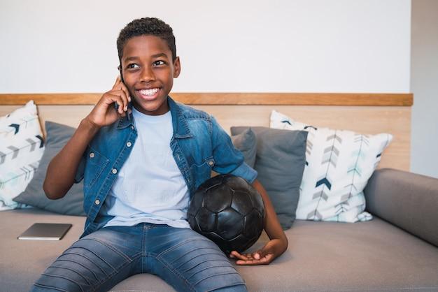 Retrato de menino falando ao telefone com alguém enquanto está sentado no sofá em casa. conceito de comunicação.