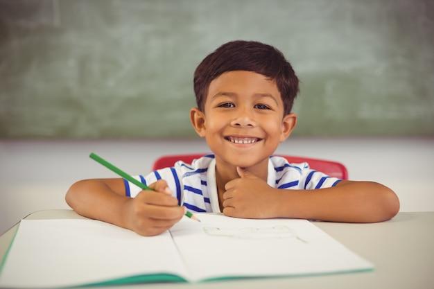 Retrato de menino fazendo lição de casa em sala de aula