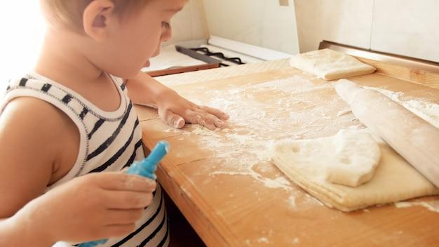 Retrato de menino fazendo massa na bancada de madeira da cozinha