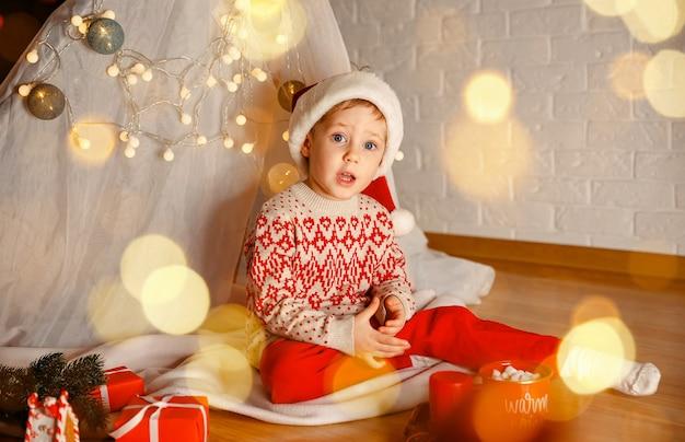 Retrato de menino feliz à noite no fundo das luzes de natal