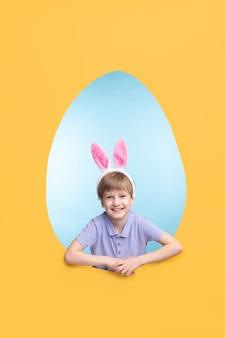 Retrato de menino feliz e animado com uma faixa de orelha de lebre em pé na moldura em forma de ovo de páscoa
