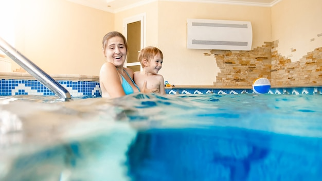 Retrato de menino feliz e sorridente, aprendendo a nadar com a mãe na piscina
