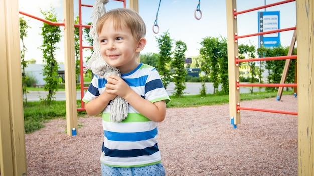 Retrato de menino feliz e sorridente, brincando com uma corda grande para escalar o palyground infantil no parque