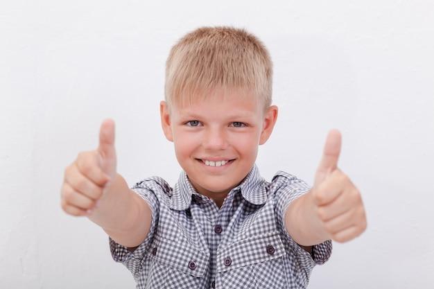 Retrato de menino feliz, mostrando os polegares para cima gesto