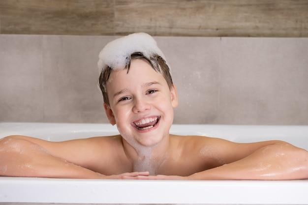 Retrato de menino feliz no banheiro criança tomando banho com espuma na cabeça