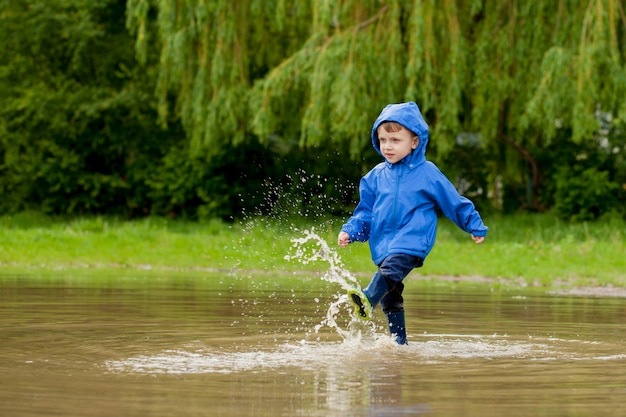 Retrato de menino garoto bonito brincando com navio artesanal. menino do jardim de infância navegando um barco de brinquedo à beira das águas no parque