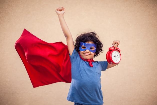Retrato de menino garoto com cabelos cacheados em traje de super-herói segurando o relógio despertador. conceito de gestão de infância, sucesso e tempo