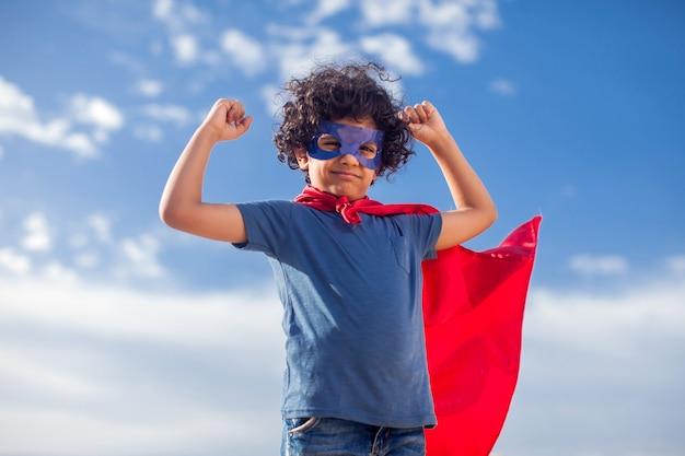 Retrato de menino garoto com cabelos cacheados em traje de super-heróis. conceito de infância e sucesso