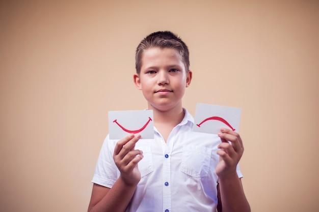 Retrato de menino garoto segurando cartas com expressão de humor. triste e bom sorriso. conceito de infância e emoção