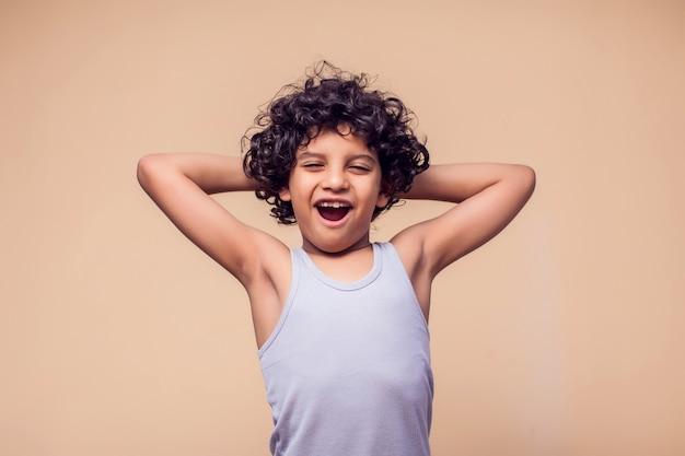 Retrato de menino garoto surpreso com cabelos cacheados. conceito de crianças e emoções