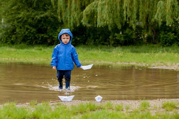 Retrato de menino lindo brincando com um navio feito à mão