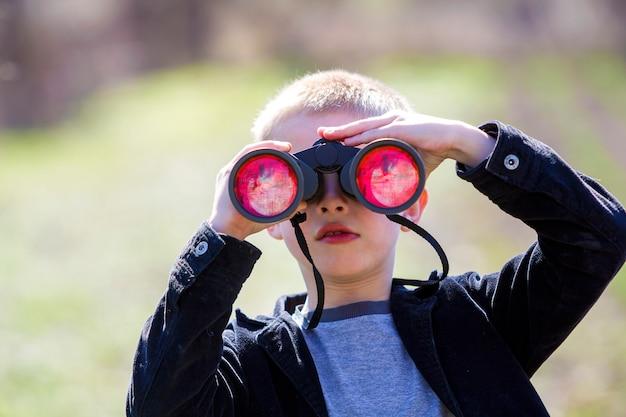 Retrato de menino loiro bonitinho bonito bonitinho assistindo atentamente algo através de binóculos